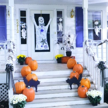 pretty white house decorated for halloween