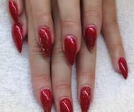 Red stiletto nails with gold glitter